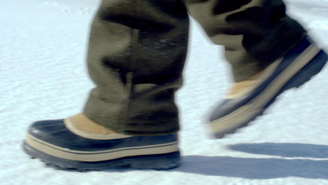 Boots walking across the snow-covered ground Footage