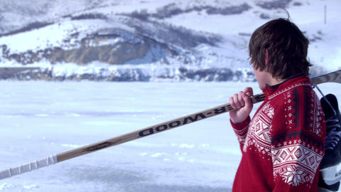 Young boy walking through snow with hockey gear Footage