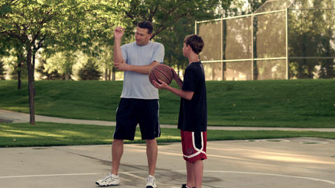 Royalty Free Stock Footage of Father and son playing basketball in a park Footage