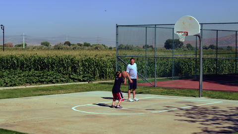 Royalty Free Stock Footage of Boy playing basketball with his dad in the park Footage