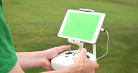 Man Uses RC Controller for UAV Drone Outside Green Screen Tablet Footage