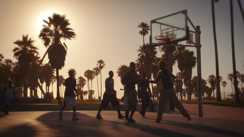 Slow motion lens flare shot of men playing basketball near Venice Beach, Califor Footage