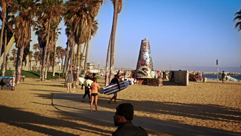 Slow motion shot of three surfers carrying surfboards walking near Venice Beach, Footage