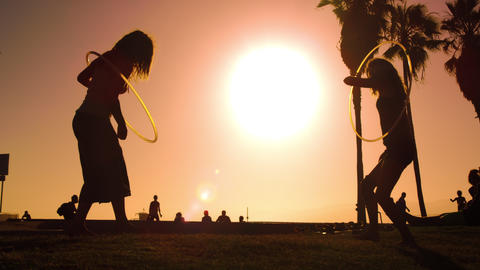 Women play with hula hoops filmed in slow motion and with lens flare near Venice Footage