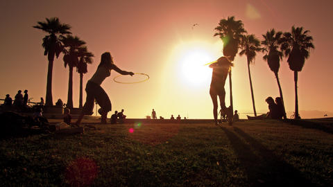 Lens flare shot of people strolling near Venice Beach, California filmed in slow Footage