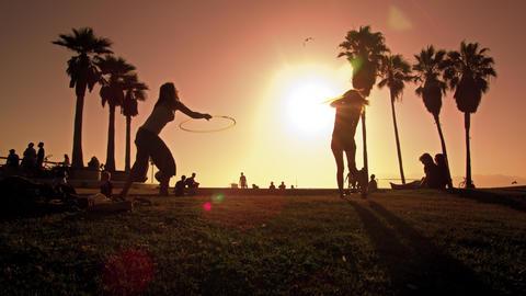 Lens flare shot of people strolling near Venice Beach, California filmed in slow Footage