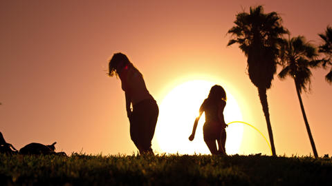 Lens flare shot of two young women playing with hula hoops near Venice Beach, Ca Footage