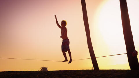 Lens flare shot of a man balancing on the slackline near Venice Beach, Californi Footage