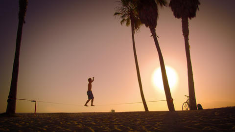 Long distance lens flare shot of a man slacklining near Venice Beach, California Footage