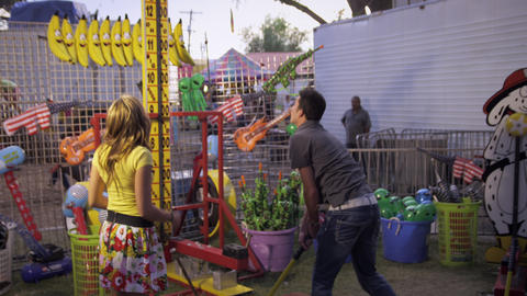 Shot of a man, with a girl, swinging a hammer at a carnival game Footage