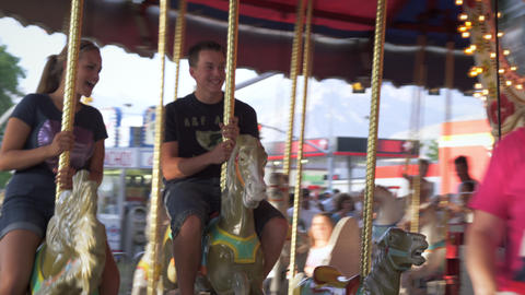 Shot of people riding around on a merry-go-round at a carnival Footage