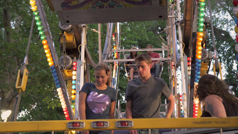 Shot of a boy and a girl getting off of a carnival ride Footage