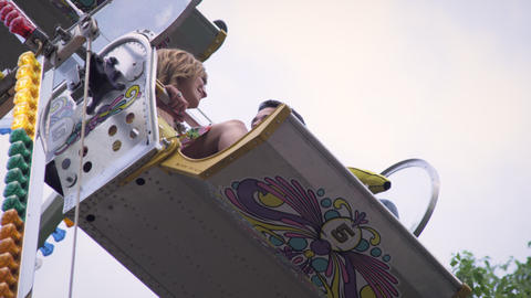 Upward shot of girl talking to boy on ferris wheel chair Footage