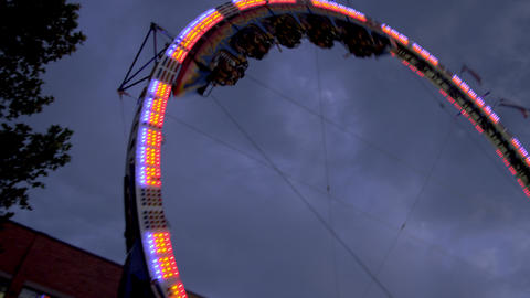 Upwards shot of people riding on a circular, vertical rollercoaster Footage