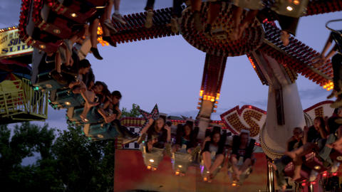 Rack focus shot of a carnival ride slowly coming to a stop Footage