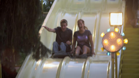 Slow motion shot of boy and girl sliging down a bumpy slide at a carnival Footage
