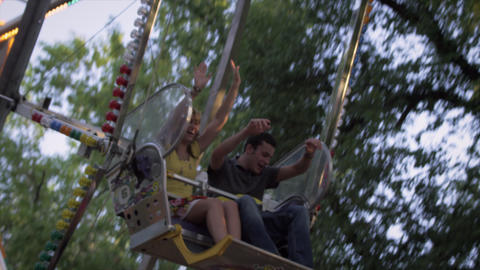 Ferris-wheel riders excitedly hold their arms up as they circle down Footage