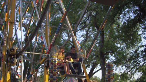 Ferris-wheel riders talk and have fun as the wheel moves them backwards and down Footage