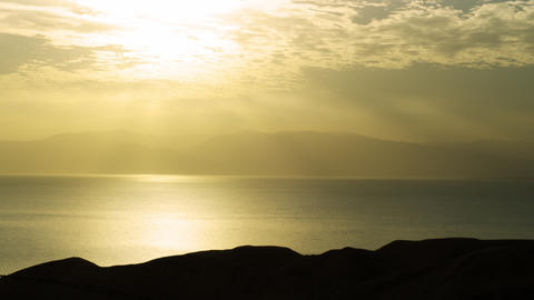 Stock Video Footage of a silhouetted foreground rock at dawn at the Dead Sea in  Footage
