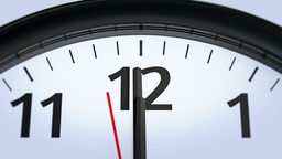Close-up video of a modern wall clock approaching twelve o'clock Footage