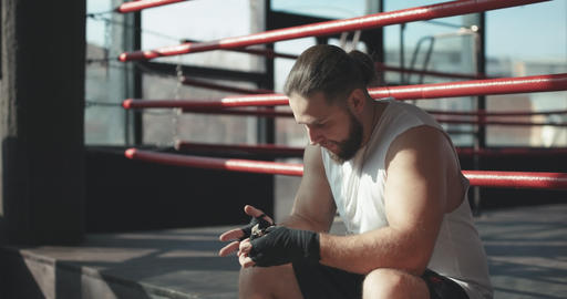 Boxer puts on hand wraps while sitting on the edge of a boxing ring in a boxing Live Action