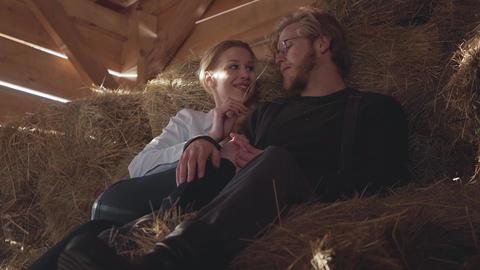 Portrait of pretty young couple lying on the hay in the cold winter barn. Young Live Action