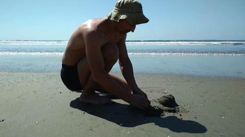 Man freaking out, crashing sand castle he try to build on the beach. Getting mad Footage