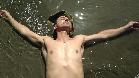 Man relaxing lay in water on the beach on the sunshine, holidays concept Footage