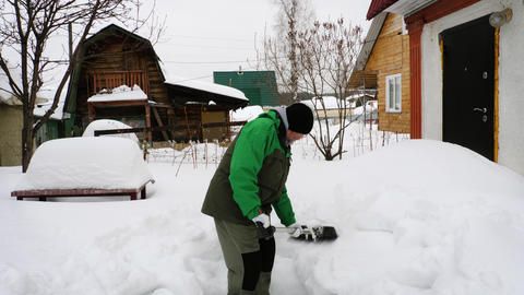 Man shoveling snow in yard Live Action