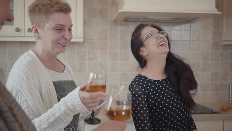 Three lovely senior women laugh out loud together while drinking wine, one Live Action