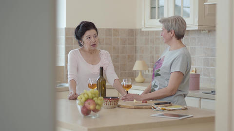 Two mature women communicating standing near modern table in the kitchen. Lady Footage