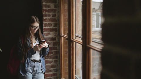 Attractive Girl Standing by Window and Texting Live Action