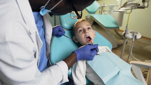 African male dentist checking the teeth of little male patient Live Action