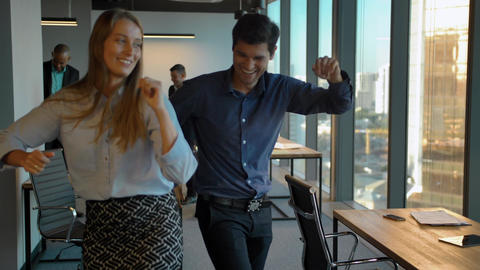 Attractive confident colleagues celebrating with dance in their office Footage