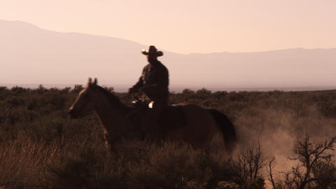 Slow motion shot of a cowboy riding from camera right across the frame to camera Footage