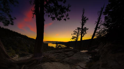 Timelapse tilting shot of the sunrise over a Emerald Bay in Nevada with lens fla Footage