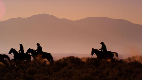 Slow motion silhouette shot of group of cowboys riding horses Footage