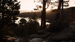 Dark shot of sun peaking through trees over water andstream near Lake Tahoe, C Footage