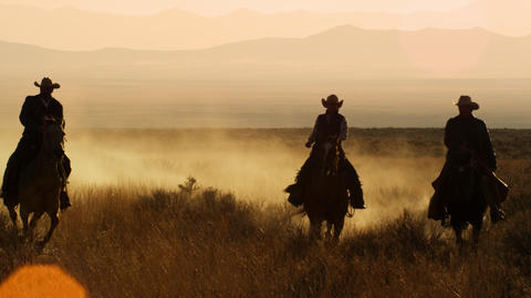 Slow motion shot of four cowboys riding in a line together Footage