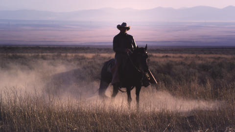 Slow motion static shot of a cowboy riding a horse in a swirl of dust Footage