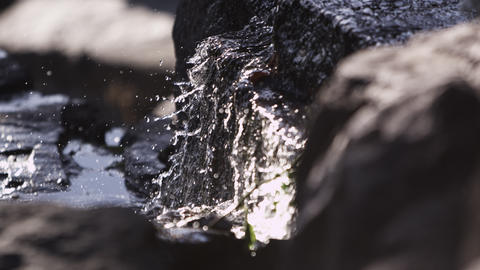 Close-up slow motion shot of water cascading over rocks Footage