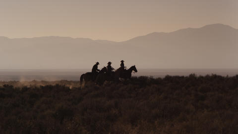 A group of 4 cowboys mosey from camera left to camera right Footage