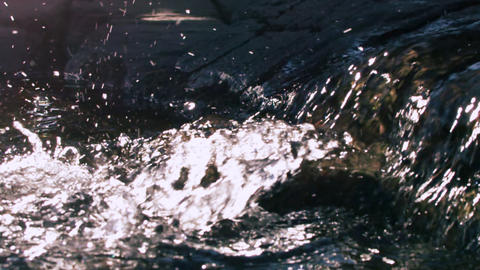 Slow motion shot of water flowing and splashing over rocks Footage