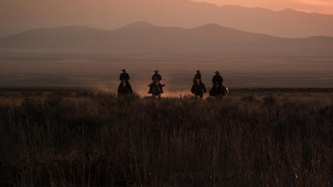 Slow motion shot of cowboys galloping in distance Footage