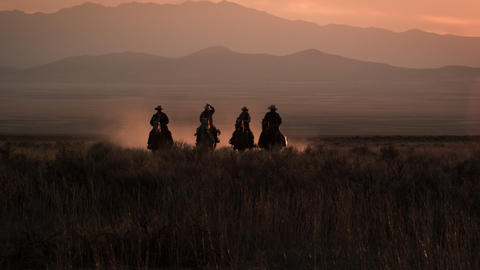 Slow motion clip of cowboys galloping in distance Footage
