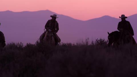 Slow motion shot of cowboys riding towards the camera with pink sky in the backg Footage