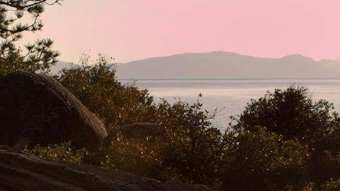 Shot of trees with mountains in distance at dusk. Shot at Emerald Bay State Park Footage