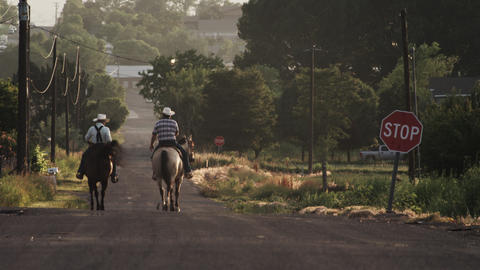 Shot of two cowboys on horseback on a street in the USA Footage