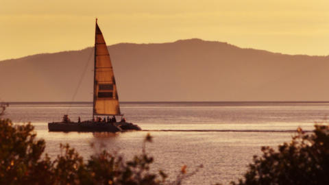 Static shot of sailboat on water with orange sky. Shot at Emerald Bay State Park Footage