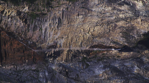 Close-up shot of mountainside with small waterfall trickling downward Footage